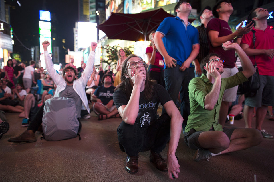 Photo -   Lennon Batchelor, 27, of Orlando, center, pauses while watching a live stream of the Mars Curiosity landing while neighboring spectators cheer in Times Square after the successful touch-down, August 6, 2012, in New York. After traveling 8 1/2 months and 352 million miles, Curiosity landed on Mars Sunday night. (AP Photo/John Minchillo)