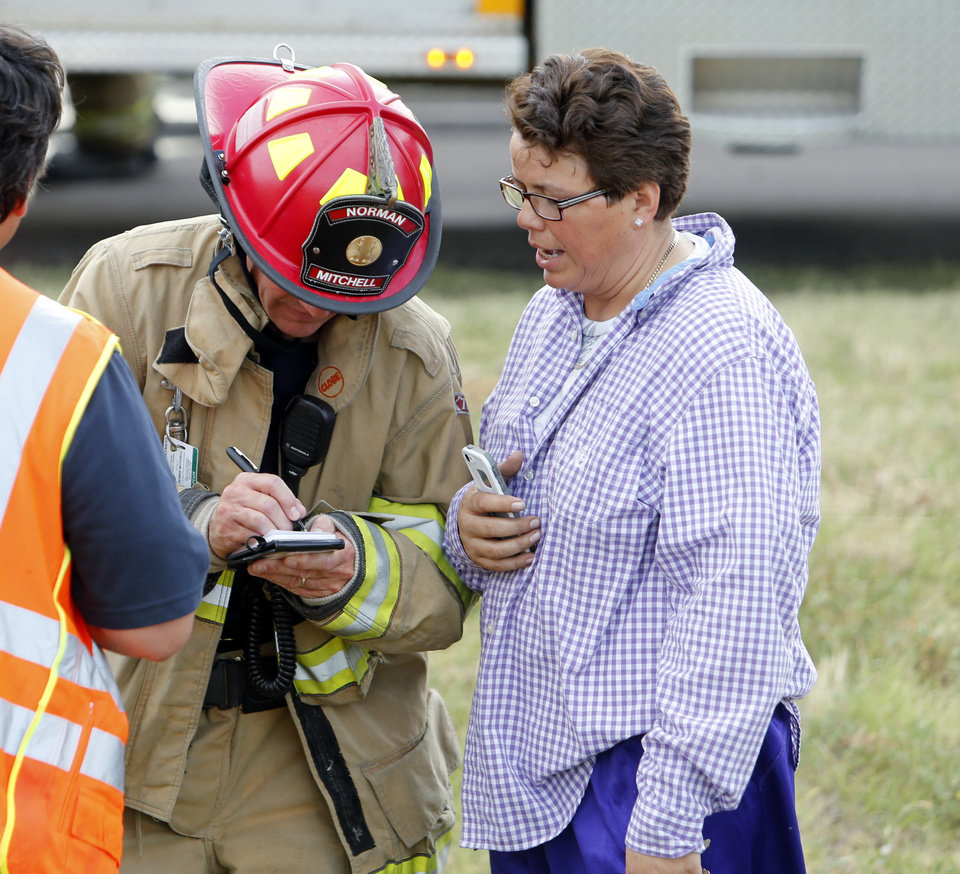 Photo - Norman fire officials interview the driver of a truck that caught fire on Interstate 35 on Wednesday, July 10, 2013 in Norman, Okla.  Photo by Steve Sisney, The Oklahoman