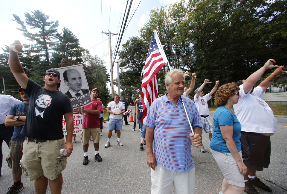 Photo - Market Basket employees and supporters jeer a car driving into the supermarket's headquarters in Tewksbury, Mass., Monday, Aug. 18, 2014. As an employee revolt at the New England grocery store chain headed into its fifth week, the governors of Massachusetts and New Hampshire made the unusual move of personally stepping into negotiations aimed at ending a standoff threatening the future of the popular low-priced supermarkets. (AP Photo/Elise Amendola)