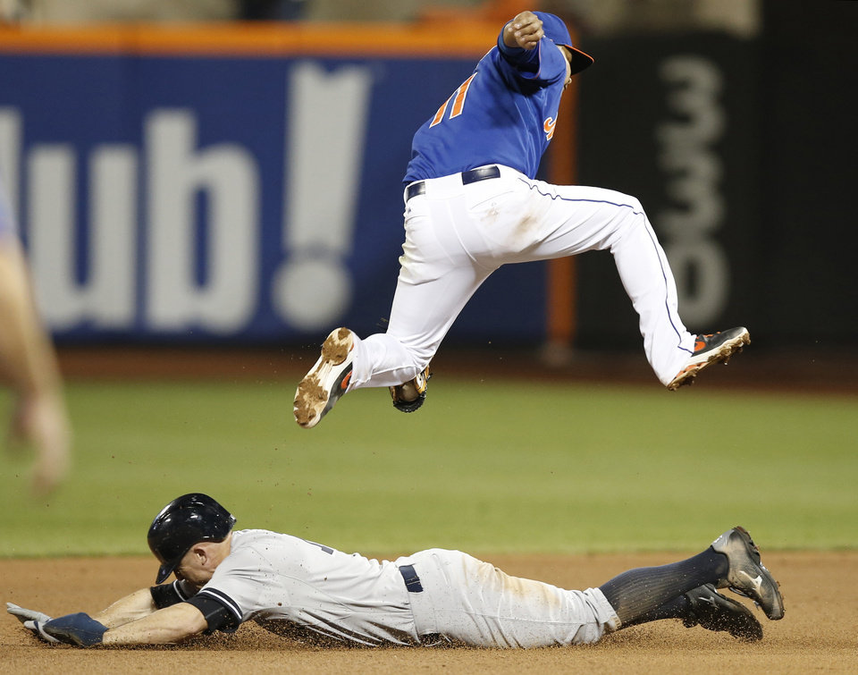 Photo - New York Mets shortstop Ruben Tejada (11) leaps to field a short throw as New York Yankees Brett Gardner steals second in the seventh inning of a baseball game against the New York Mets in New York, Wednesday, May 14, 2014. (AP Photo)
