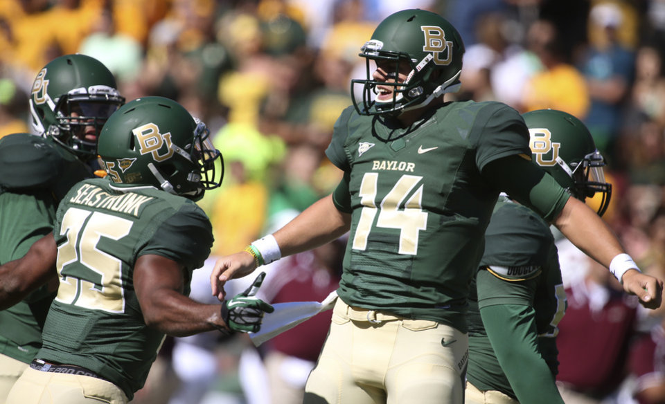 Photo - Baylor quarterback Bryce Petty (14) celebrates his touchdown against Louisiana-Monroe  with teammate Lache Seastrunk (25) during the first half of an NCAA college football game, Saturday, Sept. 21, 2013, in Waco, Texas. (AP Photo/Waco Tribune Herald, Rod Aydelotte)