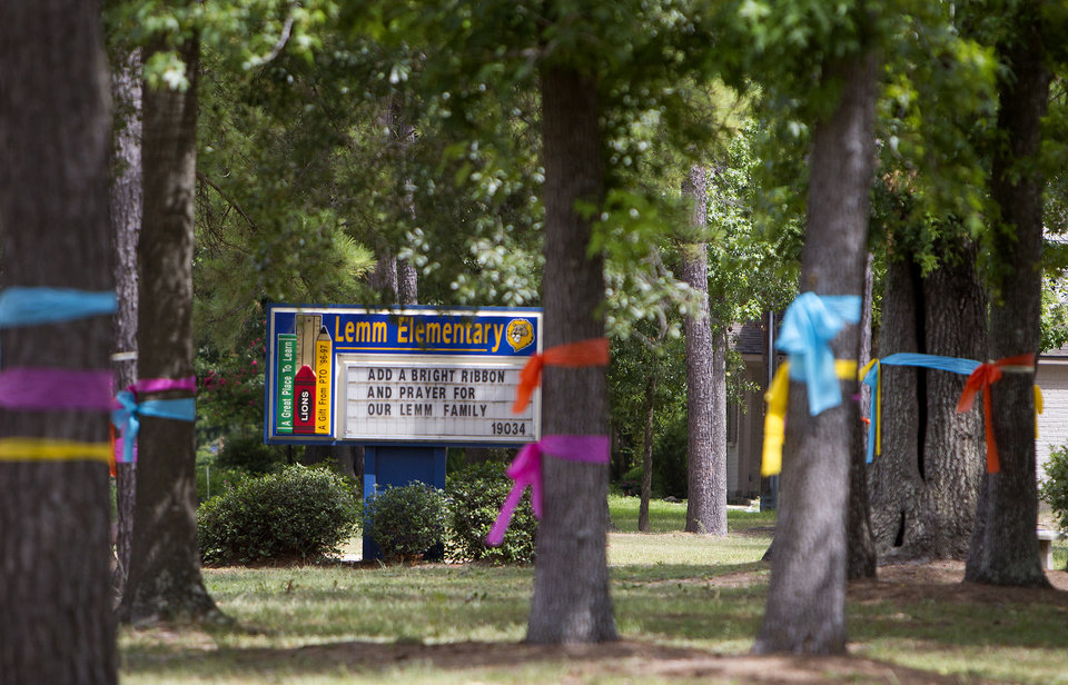Photo - Ribbons are tied around trees in front of Lemm Elementary School in Spring, Texas on Thursday, July 10, 2014. Officials said Ronald Lee Haskell, dressed as a parcel delivery man, forced his way into his sister-in-law's home near the suburban Houston school and shot her dead, along with her husband and four of their children. (AP Photo/Houston Chronicle, Cody Duty)
