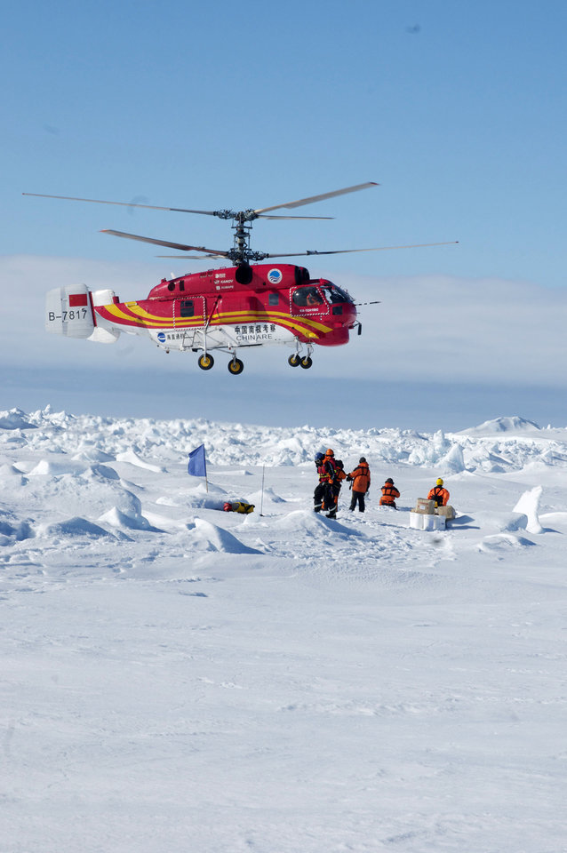 Photo - In this image provided by Australasian Antarctic Expedition, passengers trapped for more than a week on the icebound Russian research ship MV Akademik Shokalskiy are rescued by a Chinese helicopter, Thursday, Jan. 2, 2014. The helicopter rescued all 52 passengers from the research ship that has been trapped in Antarctic ice, 1,500 nautical miles south of Hobart, Australia, since Christmas Eve after weather conditions finally cleared enough for the operation Thursday. (AP Photo/Australasian Antarctic Expedition, Jessica Fitzpatrick) EDITORIAL USE ONLY, ONE TIME USE ONLY, NO ARCHIVES; NO SALES