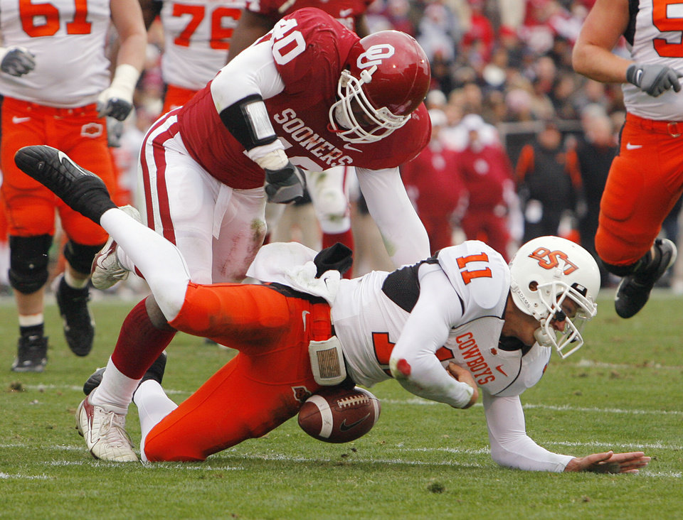 Photo - Oklahoma's Curtis Lofton (40) takes down Oklahoma State quarterback Zac Robinson (11) causing a fumble during the first half of the college football game between the University of Oklahoma Sooners (OU) and the Oklahoma State University Cowboys (OSU) at the Gaylord Family-Memorial Stadium on Saturday, Nov. 24, 2007, in Norman, Okla. 