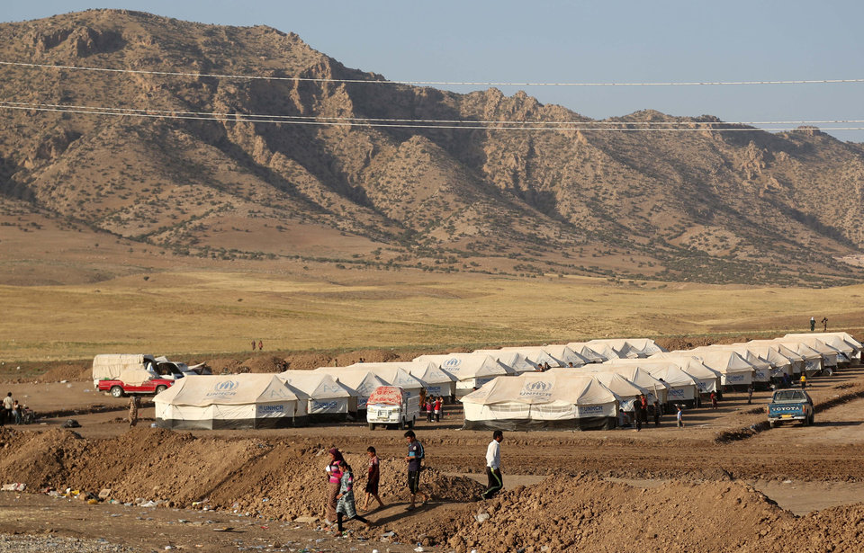 Photo - Displaced Iraqis from the Yazidi community settle at a new camp outside the old camp of Bajid Kandala at Feeshkhabour town near the Syria-Iraq border, Iraq, Friday, Aug. 15, 2014. The U.N. this week declared the situation in Iraq a