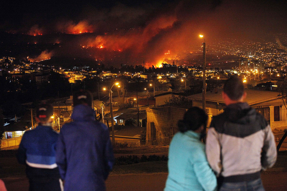 Photo - People watch as a forest fire rages towards urban areas in the city of Valparaiso, Chile, Saturday April 13, 2014. Authorities say the first fire has destroyed at least 150 homes and is forcing evacuations. ( AP Photo/ Luis Hidalgo)