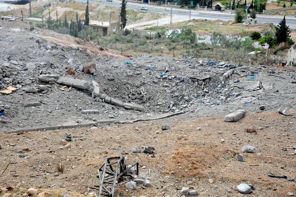 Photo - This photo released by the Syrian official news agency SANA, shows a general view of damaged buildings wrecked by an Israeli airstrike, in Damascus, Syria, Sunday, May 5, 2013. Israeli warplanes struck areas in and around the Syrian capital early Sunday, setting off a series of explosions as they targeted a shipment of highly accurate, Iranian-made guided missiles believed to be on their way to Lebanon's Hezbollah militant group, officials and activists said. The attack, the second in three days, signaled a sharp escalation of Israel's involvement in Syria's bloody civil war. Syria's state media reported that Israeli missiles struck a military and scientific research center near the Syrian capital and caused casualties. (AP Photo/SANA)