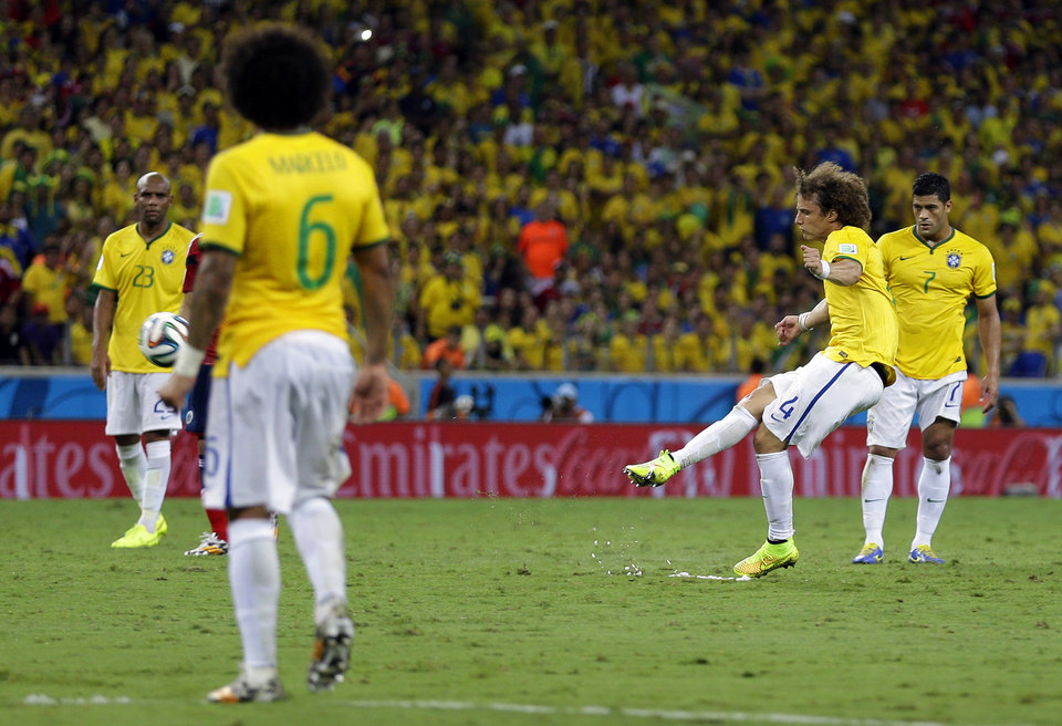 Photo - FILE - In this July 4, 2014 file photo, Brazil's David Luiz takes a free kick and scores his side's second goal during the World Cup quarterfinal soccer match between Brazil and Colombia at the Arena Castelao in Fortaleza, Brazil. Lining up 35 meters (yards) out, the 27-year-old Brazilian side-footed the ball with his right boot, sending it over a defensive wall of four and beyond the reach of Colombia goalkeeper David Ospina. (AP Photo/Natacha Pisarenko, File)