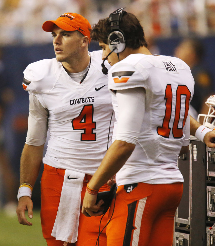 Photo - OSU quarterbacks J.W. Walsh (4) and Clint Chelf (10) stand in the bench area during a college football game between the University of Texas at San Antonio Roadrunners (UTSA) and the Oklahoma State University Cowboys (OSU) at the Alamodome in San Antonio, Saturday, Sept. 7, 2013. OSU won, 56-35. Photo by Nate Billings, The Oklahoman