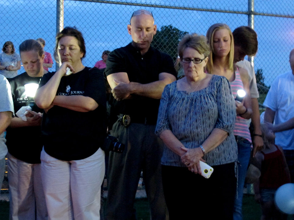 Photo -   Hundreds of adults, teens and children attend a prayer vigil at Bolivar Dixie Youth Park, where missing sisters, Alexandra Bain, 12, and Kyliyah Bain, 8, used to play softball in Bolivar, Tenn., Tuesday, May, 8, 2012. Mourners sang songs and bowed their heads in prayer as they held red, yellow, orange and purple balloons during the ceremony, as the hunt continued for a Mississippi man suspected of killing the sisters' mother, Jo Ann Bain, 31, and older sister, Adrienne Bain, 14, before fleeing with the two younger girls. (AP Photo/Adrian Sainz)