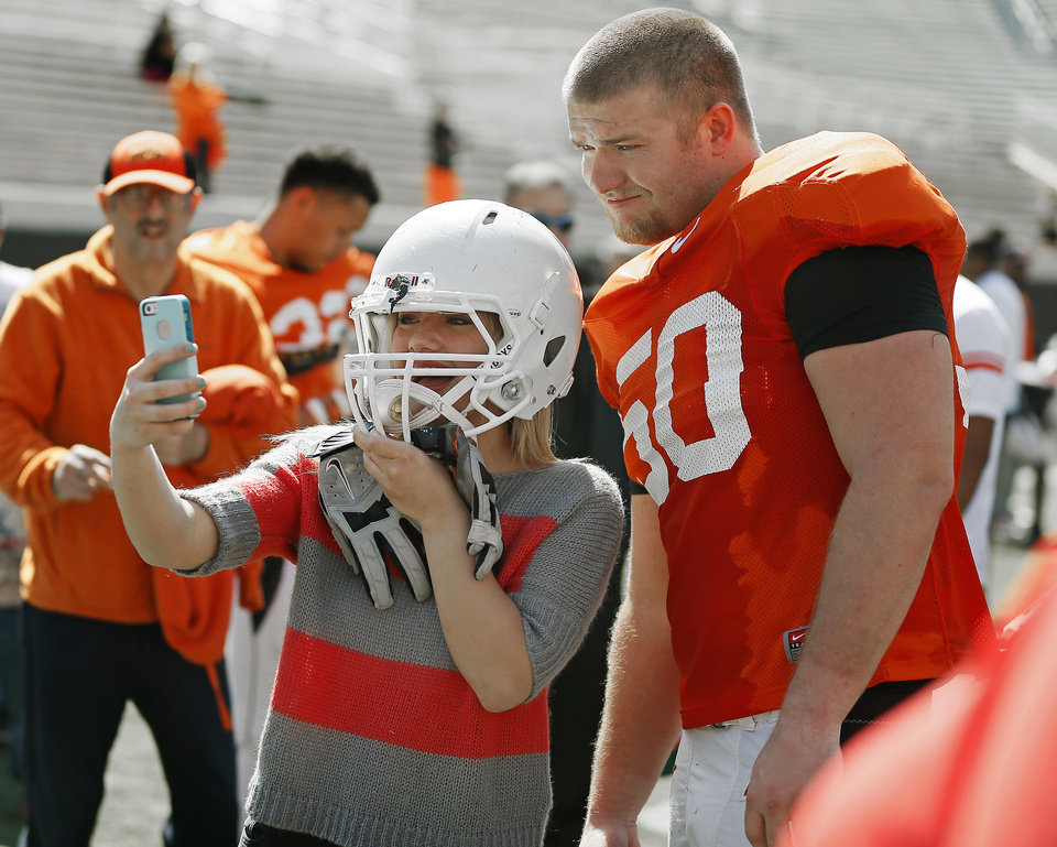 Photo - Oklahoma State sophomore Hunter Bell takes a photo of herself with OSU's Zac Veatch after Oklahoma State's Orange Blitz football practice at Boone Pickens Stadium in Stillwater, Okla., Saturday, April 5, 2014.