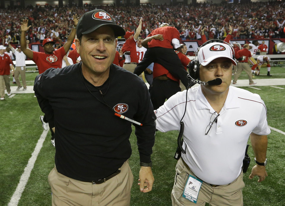 San Francisco 49ers head coach Jim Harbaugh runs onto the field with an assistant after the NFL football NFC Championship game against the Atlanta Falcons Sunday, Jan. 20, 2013, in Atlanta. The 49ers won 28-24 to advance to Superbowl XLVII. (AP Photo/Dave Martin)