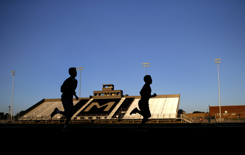 Photo - People run on the track at  Muleshoe High School's stadium in Muleshoe, Texas, hometown of Oklahoma's new offensive coordinator Lincoln Riley, on Wednesday, June 24, 2015. Photo by Bryan Terry, The Oklahoman