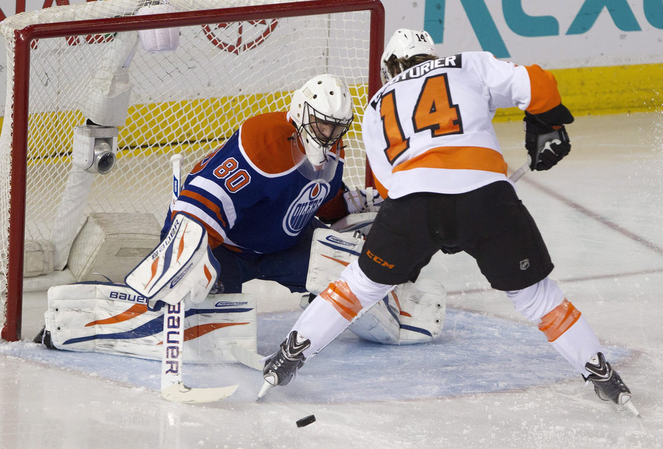 Philadelphia Flyers' Sean Couturier (14) is stopped by Edmonton Oilers goalie Ilya Bryzgalov (80) during second period NHL hockey action in Edmonton, Alberta, on Saturday, Dec. 28, 2013. (AP Photo/The Canadian Press, Jason Franson)
