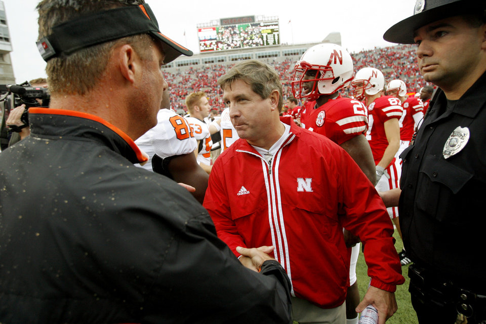 Photo - OSU head coach Mike gundy, left, shakes hands with Nebraska head coach Bill Callahan after the college football game between Oklahoma State University (OSU) and the University of Nebraska (NU) at Memorial Stadium in Lincoln, Neb., Saturday, October 13, 2007. OSU won, 45-14. By Nate Billings, The Oklahoman