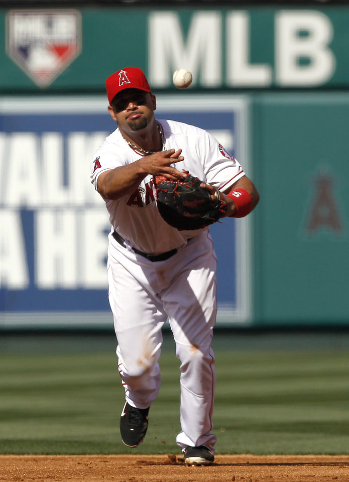 Los Angeles Angels first baseman Albert Pujols throws out Oakland Athletics' Daric Barton during the second inning of a baseball game in Anaheim, Calif., Tuesday, May 15, 2012. (AP Photo/Chris Carlson)