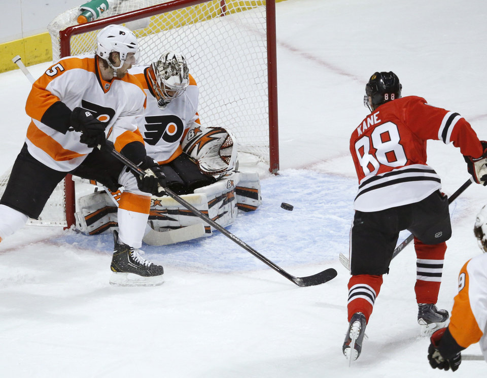 Photo - Philadelphia Flyers goalie Ray Emery, center, makes a save on a shot by Chicago Blackhawks right wing Patrick Kane (88) as Flyers' Braydon Coburn (5) also defends during the first period of an NHL hockey game on Wednesday, Dec. 11, 2013, in Chicago. (AP Photo/Charles Rex Arbogast)