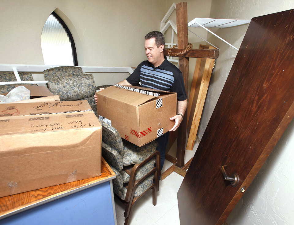 Photo - The Rev. Steve Eden, senior pastor of Grace Church, removes a box from a room behind the baptistery that is being used for storage at the  church, 100 S Choctaw Road. Photo by Jim Beckel, THE OKLAHOMAN