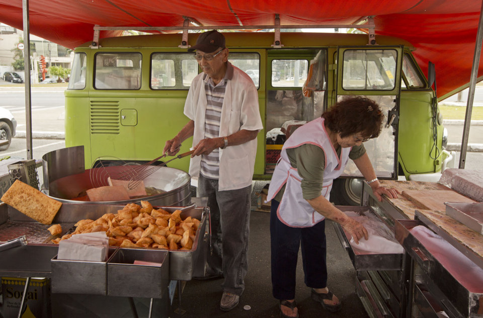 Photo - In this Sept. 3, 2013 photo, Jorge Hanashiro and his wife Ana, prepare deep fried meat and vegetable pastry pies at an open-air market, with their light green 1974 Volkswagon van or Kombi, parked nearby, in Sao Paulo, Brazil.