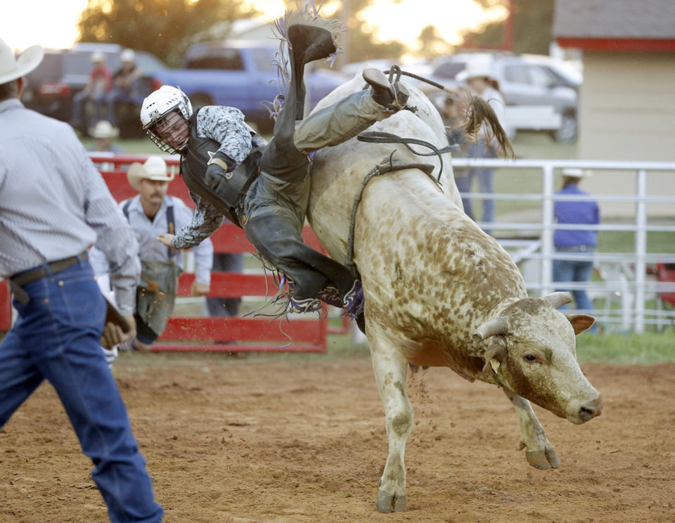 Colter White, of Liberal, Kan., falls during the bull riding competition in the annual LibertyFest Rodeo in Edmond. PHOTO BY BRYAN TERRY, THE OKLAHOMAN. <strong>Bryan Terry - THE OKLAHOMAN</strong>