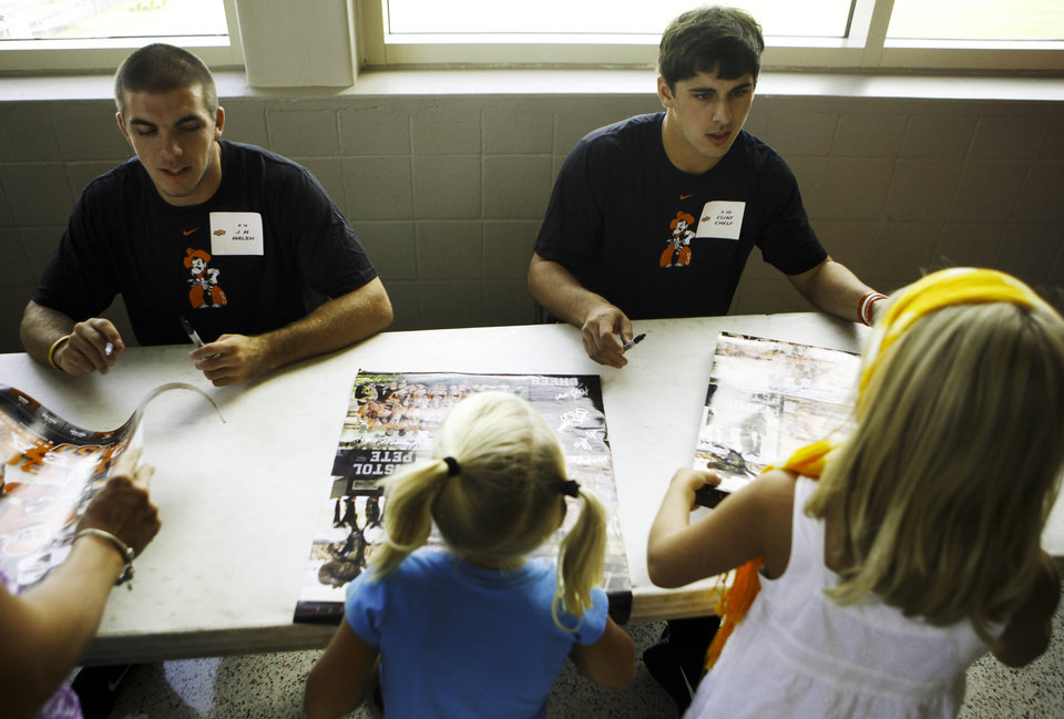 Photo - J.W. Walsh, left, and Clint Chelf, right, sign autographs for young fans at fan appreciation day at Gallagher-Iba Arena in Stillwater on August 3, 2013. KT King, For The Oklahoman