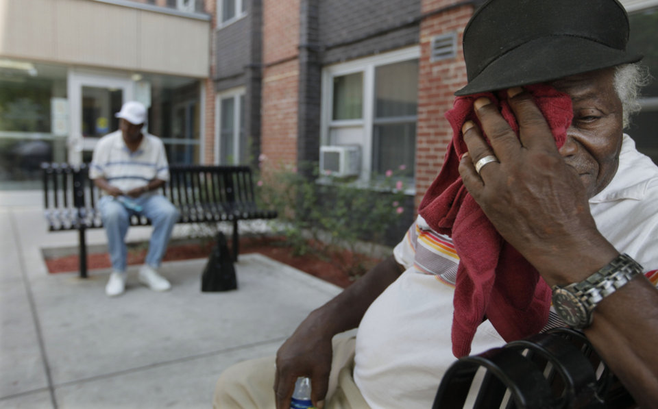Photo -   Despite triple digit temperatures and having an air conditioned apartment, eighty-year-old William Holman makes several trips a day to the courtyard at Apartamentos Las Americas to visit with his neighbors and catch some fresh air. Holman sat outside with friends as The Chicago Housing Authority conducted well-being checks on its frail and elderly residents in the building Friday, July 6, 2012, in Chicago. The CHA has made almost 44,000 since Chicago's heat wave began on Monday, July 2. (AP Photo/M. Spencer Green)