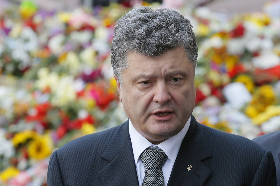 Photo - Ukrainian President, Petro Porosheko, speaks to the media after giving his condolences outside the Dutch Embassy in Kiev, Ukraine, Monday, July 21, 2014. President Poroshenko has declared a demilitarized zone around the crash site of Malaysian Airlines flight MH17.  (AP Photo)
