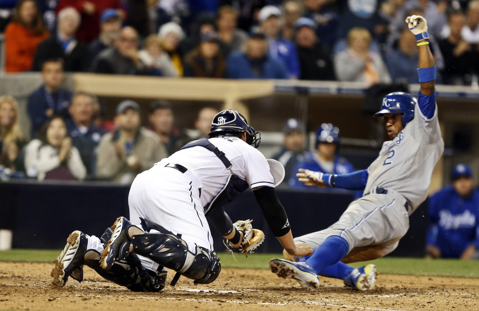 Photo - San Diego Padres catcher Yasmani Grandal dives to make a tag on Kansas City Royals' Alcides Escobar, right, who was out trying to score from third on a pop out down the right field line during the ninth inning of a tied baseball game Tuesday, May 6, 2014, in San Diego. (AP Photo/Lenny Ignelzi)