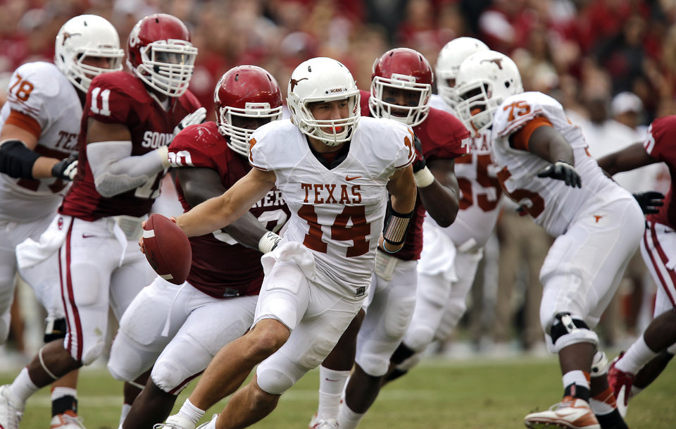 Photo - UT's David Ash (14) tries to out run the Sooner defense during the Red River Rivalry college football game between the University of Oklahoma (OU) and the University of Texas (UT) at the Cotton Bowl in Dallas, Saturday, Oct. 13, 2012. Photo by Chris Landsberger, The Oklahoman