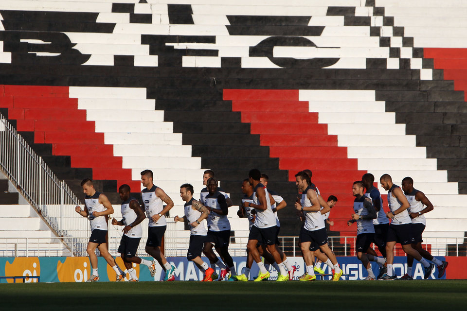 Photo - Players of the French national soccer team run on the field during a training session at the Santa Cruz stadium in Ribeirao Preto, Brazil, Sunday, June 22, 2014. Having captured people's attention at the soccer World Cup with some scintillating attacking football, France's players are now in unknown territory after raising expectations back home, having routed Switzerland and Honduras. (AP Photo/David Vincent)