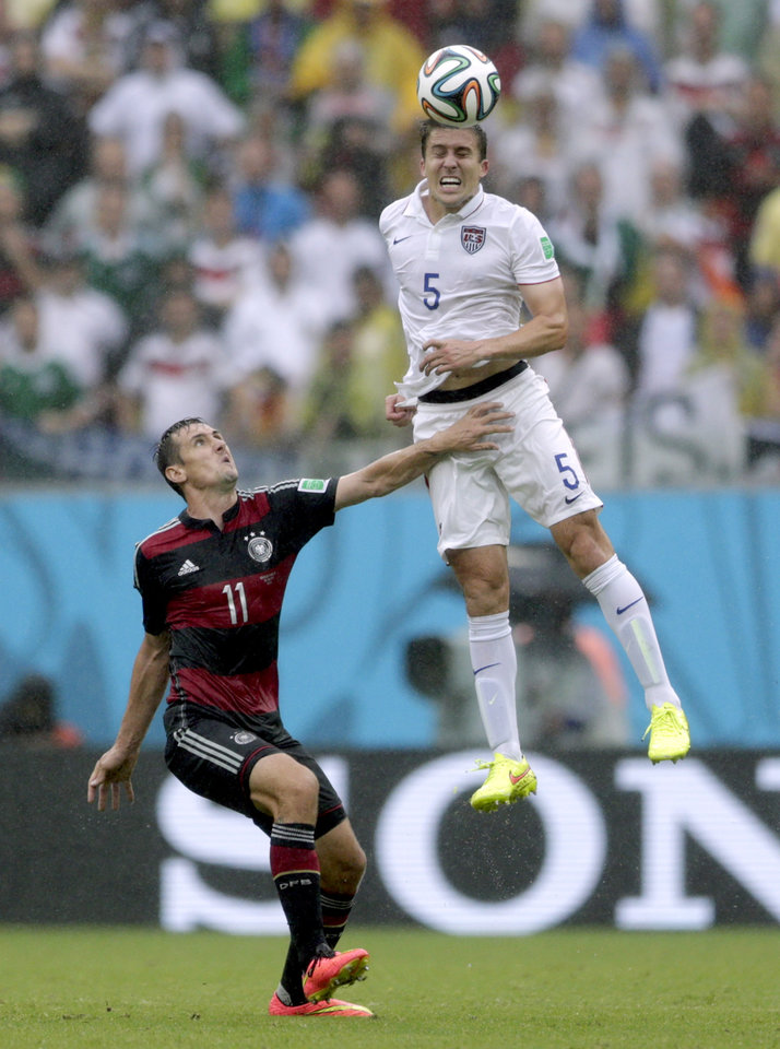 Photo - United States' Matt Besler goes up to head the ball over Germany's Miroslav Klose during the group G World Cup soccer match between the United States and Germany at the Arena Pernambuco in Recife, Brazil, Thursday, June 26, 2014. (AP Photo/Julio Cortez)