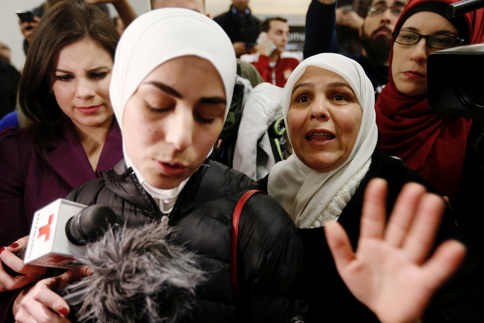 Photo - Mariam Yasin, left, translates for her mother Najah Alshamieh, 55, from Syria, after immigration authorities released Alshamieh at Dallas Fort-Worth airport, Saturday, Jan. 28, 2017. Alshamieh was held by immigration authorities after President Donald Trump signed an executive order barring muslims from certain countries from entering the Unties States. (Brandon Wade/Star-Telegram via AP)