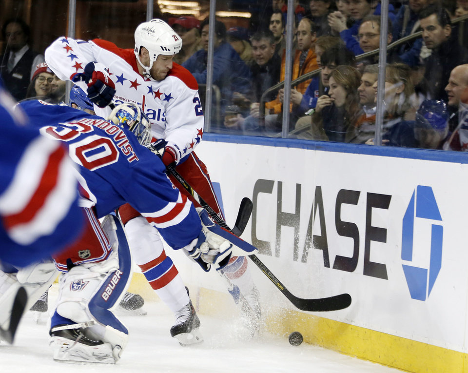 Photo - New York Rangers goalie Henrik Lundqvist (30) leaves the crease to defend Washington Capitals center Brooks Laich (21) in the first period of an NHL hockey game at Madison Square Garden in New York, Sunday, Jan. 19, 2014. (AP Photo/Kathy Willens)