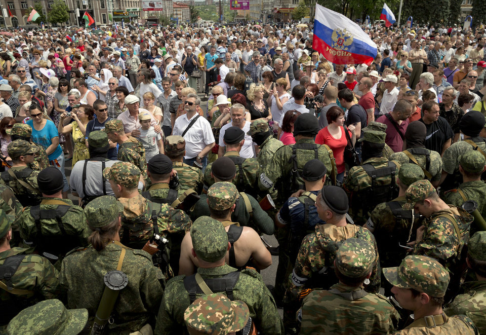 Photo - Crowds cheer pro-Russian gunmen in Lenin square in Donetsk, Ukraine, Sunday, May 25, 2014. A convoy of an armored personnel carriers and seven trucks carrying several hundred heavily armed men drove through central Donetsk early Sunday afternoon and gunmen got out of the trucks, stood to attention and shot in the air in jubilation as a crowd of several thousand supporters cheered them and chanted: