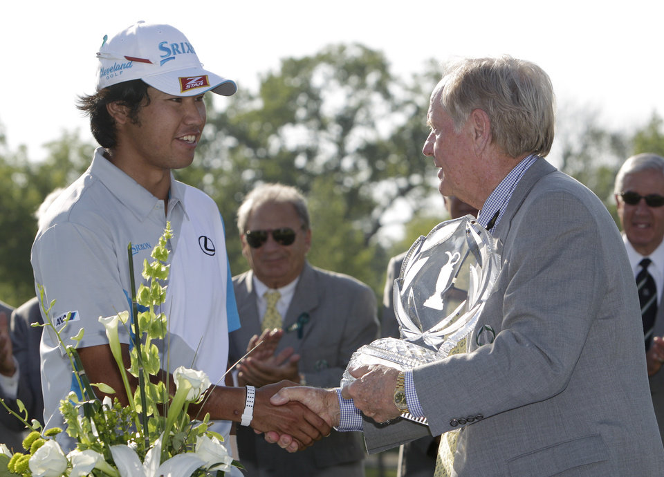 Photo - Jack Nicklaus, right, presents Hideki Matsuyama, of Japan, with the trophy after Matsuyama won the Memorial golf tournament on the first playoff hole Sunday, June 1, 2014, in Dublin, Ohio. (AP Photo/Jay LaPrete)