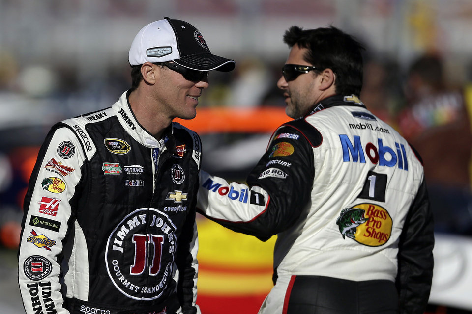 Photo - Kevin Harvick, left, talks with Tony Stewart during qualifying for Sunday's NASCAR Sprint Cup Series auto race on Friday, March 7, 2014, in Las Vegas. (AP Photo/Isaac Brekken)