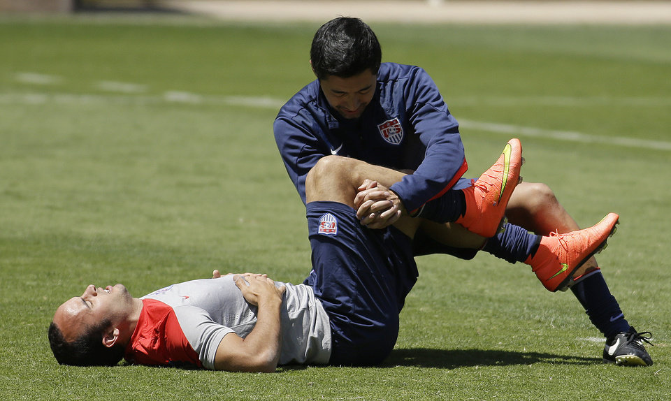 Photo - U.S. forward Landon Donovan is assisted in stretching by a trainer during training for the World Cup soccer tournament Thursday, May 22, 2014, in Stanford, Calif. Donovan was cut from the roster later Thursday for the World Cup. (AP Photo/Ben Margot)