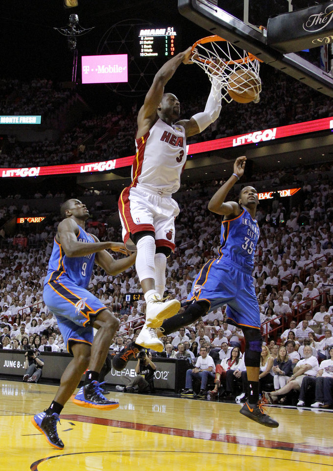 Photo - Miami's Dwyane Wade (3) dunks the ball between Oklahoma City's Serge Ibaka (9) and Kevin Durant (35) during Game 3 of the NBA Finals between the Oklahoma City Thunder and the Miami Heat at American Airlines Arena, Sunday, June 17, 2012. Oklahoma City lost 91-85. Photo by Bryan Terry, The Oklahoman