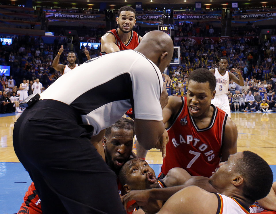 Photo - Oklahoma City's Serge Ibaka (9) argues for a jump ball beside Toronto's Kyle Lowry (7) and DeMarre Carroll (5) during an NBA basketball game between the Oklahoma City Thunder and the Toronto Raptors at Chesapeake Energy Arena on Wednesday, Nov. 4, 2015. The Thunder lost 103-98. Photo by Bryan Terry, The Oklahoman