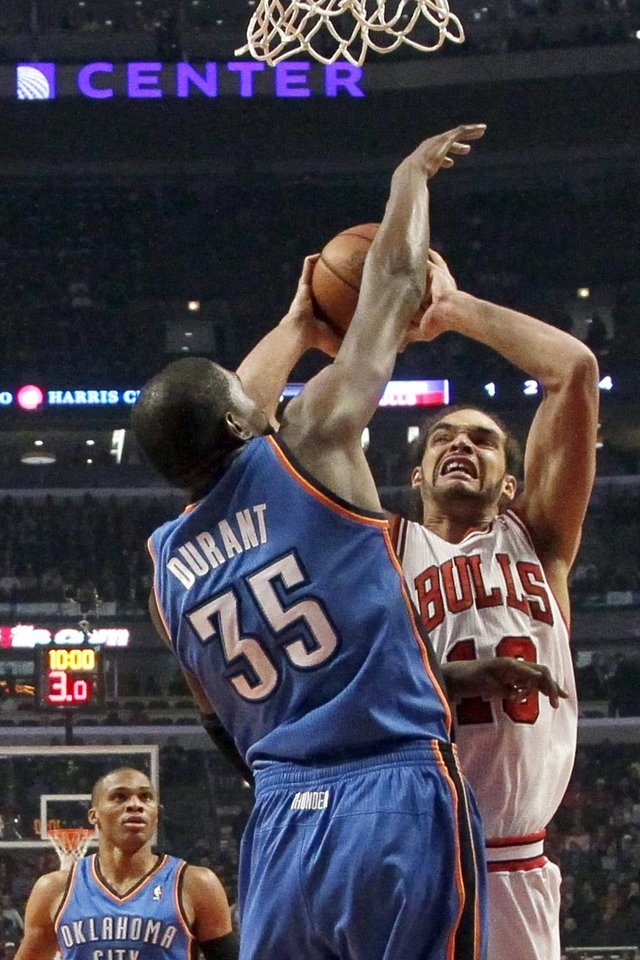 Chicago Bulls center Joakim Noah (13) shoots over Oklahoma City Thunder forward Kevin Durant (35) as Russell Westbrook (0) watches during the first half of an NBA basketball game, Thursday, Nov. 8, 2012, in Chicago. (AP Photo/Charles Rex Arbogast)