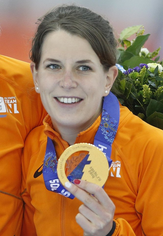 Photo - Ireen Wust of the Netherlands celebrates with her gold medal on the podium of the women's team pursuit at the Adler Arena Skating Center at the 2014 Winter Olympics, Saturday, Feb. 22, 2014, in Sochi, Russia. Wust became the first athlete at these Winter Games with five medals, two gold and three silvers. (AP Photo/Patrick Semansky)