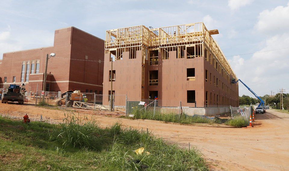 Photo -  Construction of new affordable apartments continues immediately east of the former Page Woodson School, which also is being renovated into housing and community space. [Photo by Nate Billings, The Oklahoman]