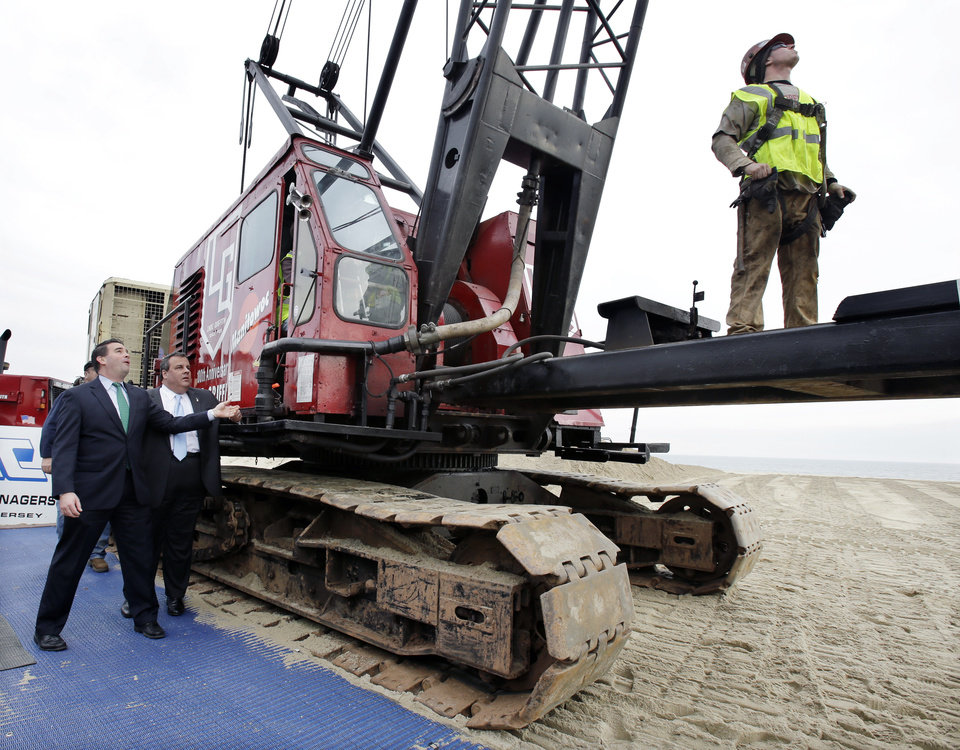 Photo - Belmar Mayor Matt Doherty, left, and New Jersey Gov. Chris Christie react, Wednesday, Jan. 9, 2013, in Belmar, N.J., as they pull a lever to start a piledriver machine to drive-in the first piling to begin Belmar's construction on a 1.3-mile boardwalk to replace the walkway destroyed by Superstorm Sandy in October. The goal is to have it done by May. Mayor Doherty says new designs including the use of strong hurricane tie-down straps will help anchor the new boardwalk to its support moorings. The town intended to rebuild the boardwalk with tropical rain forest wood but abandoned those plans Tuesday, saying it wanted to avoid a protracted legal battle with environmentalists. (AP Photo/Mel Evans)