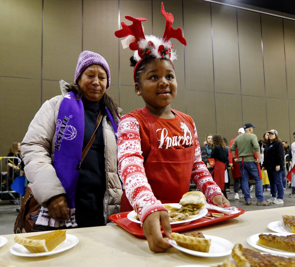 Photo -  Volunteer Kendra Lange, 8, from Edmond, helps Oni Xanders gather her Christmas Dinner during last year's Red Andrews Christmas Dinner at the Cox Convention Center. [Oklahoman Archives Photo]