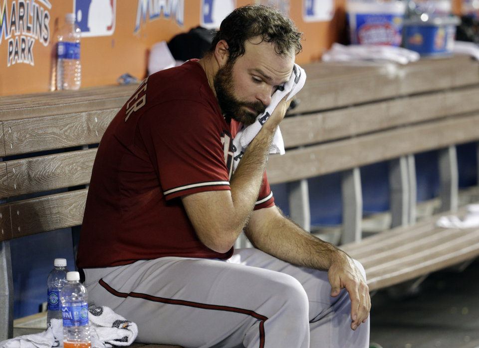 Photo - Arizona Diamondbacks starting pitcher Josh Collmenter wipes his face after pitching in the fourth inning during a baseball game against the Arizona Diamondbacks, Sunday, Aug. 17, 2014, in Miami. (AP Photo/Lynne Sladky)