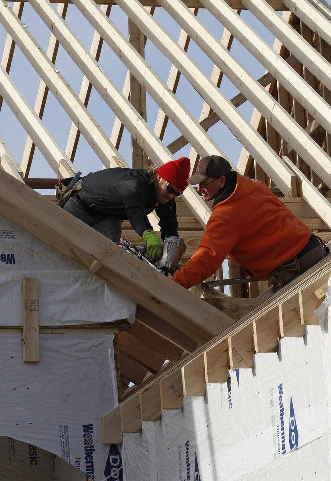 Photo - In this Thursday, Dec. 6, 2012, photo a new home is constructed in Pepper Pike, Ohio. US home construction surges 12.1 percent in December to end best year since 2008. (AP Photo/Tony Dejak)