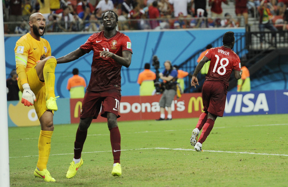 Photo - United States' goalkeeper Tim Howard, left, stands near the post as he reacts next to Portugal's Eder, second from left, after Portugal's Silvestre Varela, right, scored the equaliser during the group G World Cup soccer match between the USA and Portugal at the Arena da Amazonia in Manaus, Brazil, Sunday, June 22, 2014. (AP Photo/Paulo Duarte)