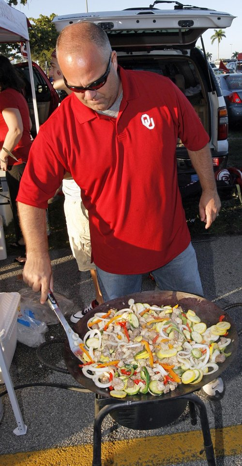 Photo - Mike Lutts, of Oklahoma City, cooks in the parking lot before the BCS National Championship college football game between the University of Oklahoma Sooners (OU) and the University of Florida Gators (UF) on Thursday, Jan. 8, 2009, at Dolphin Stadium in Miami Gardens, Fla. PHOTO BY NATE BILLINGS, THE OKLAHOMAN