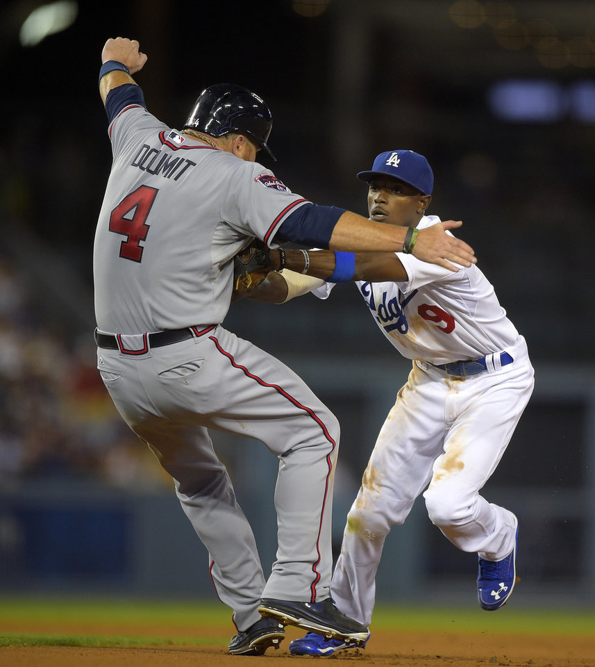 Photo - Los Angeles Dodgers second baseman Dee Gordon, right, tags Atlanta Braves' Ryan Doumit out as Doumit runs to second on a ball hit by Andrelton Simmons during the eighth inning of a baseball game, Thursday, July 31, 2014, in Los Angeles. Simmons was thrown out at first on the play. (AP Photo/Mark J. Terrill)