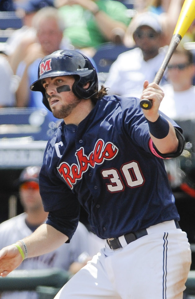 Photo - Mississippi's Will Allen follows the ball he hit with the bases loaded get caught by Virginia third baseman Kenny Towns to end the third inning of an NCAA baseball College World Series game in Omaha, Neb., Saturday, June 21, 2014. (AP Photo/Eric Francis)